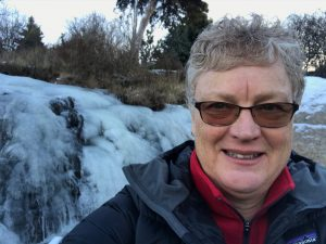 Dana Wagner, Interim Co-Director of Hawthorne Valley Farm, standing outside in front of a frozen waterfall