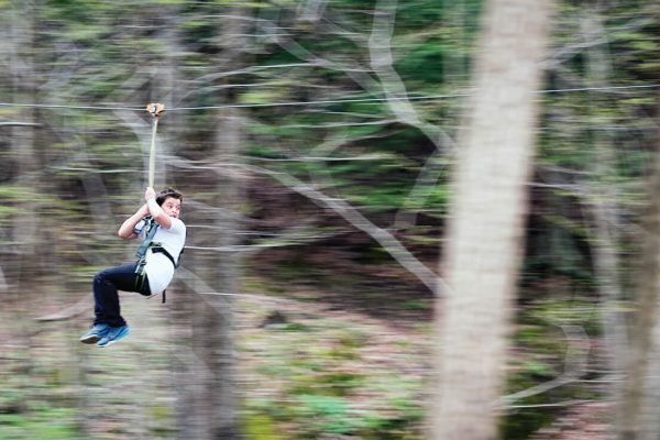 boy riding zipline behind school during May Day festival