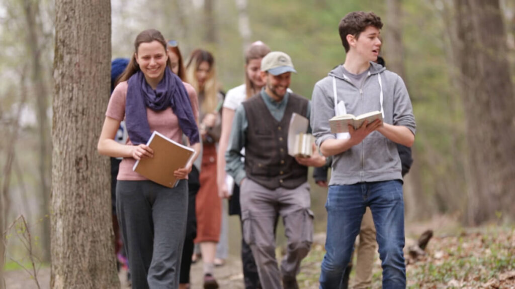 High school students walk through woods with teacher