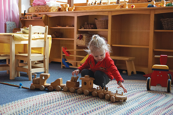 Young child playing with wooden train