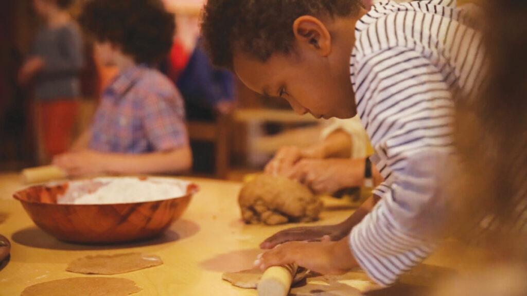 Child in kindergarten rolling dough